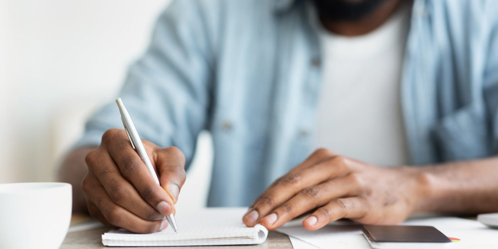 Unrecognizable African American Self-Employee Writing Down His Plans To Notepad. Closeup with copy space