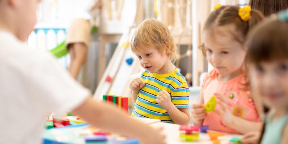 Group of children playing together in the classroom in kindergarten or preschool